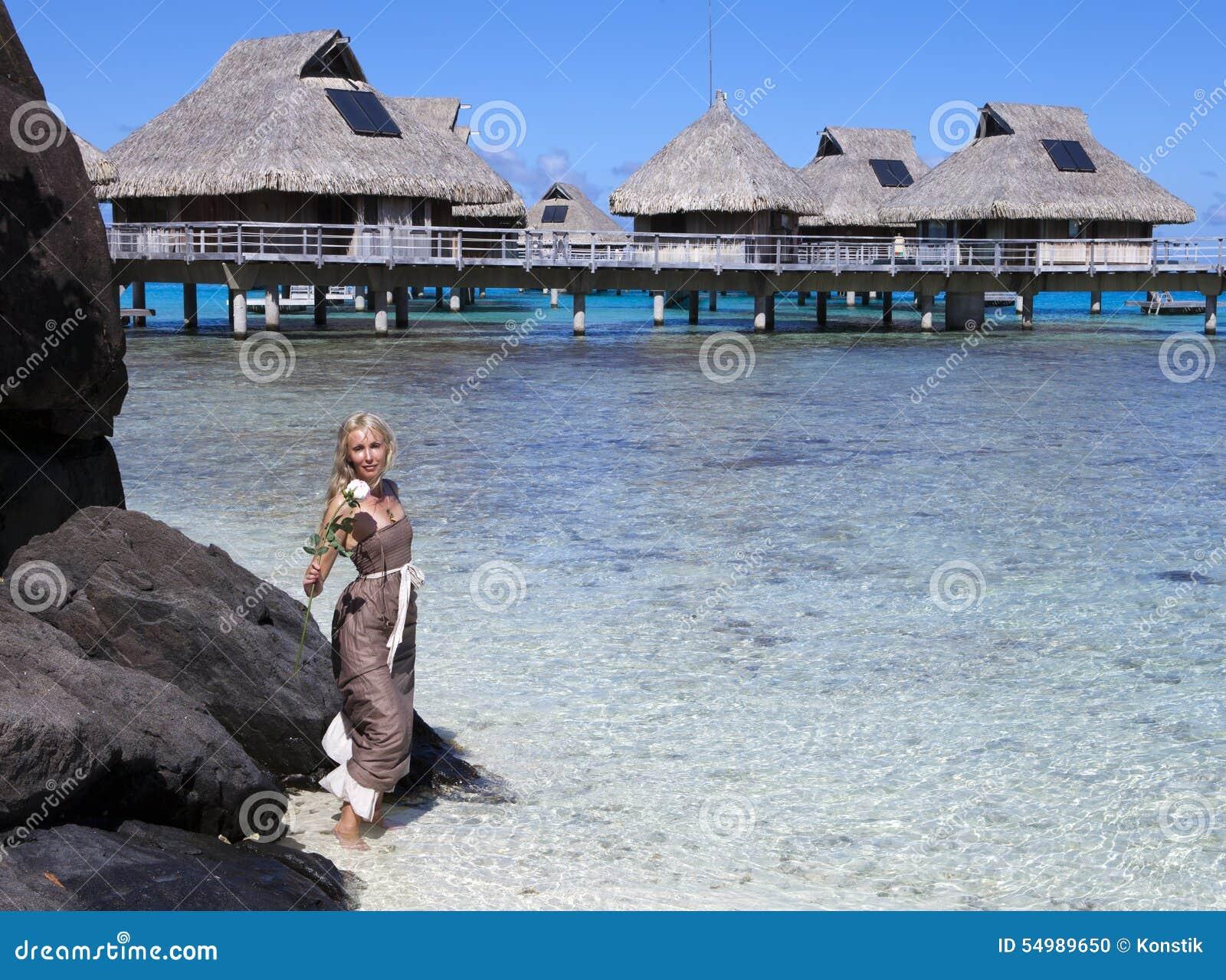 Kvinna i en lång klänning med en ros i hand i havet och de traditionella kojorna på bakgrund