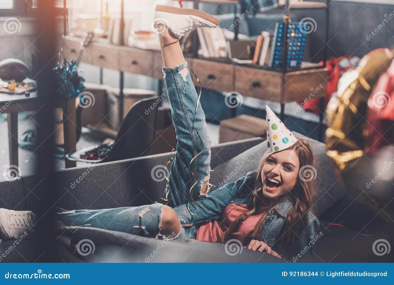 Kvinna i födelsedaghattsammanträde på soffan i smutsigt rum efter parti