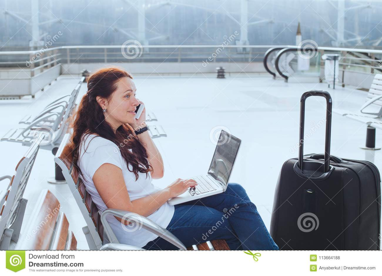 Kvinna i flygplats som talar vid telefonen och kontrollerar emails på bärbara datorn, affärslopp
