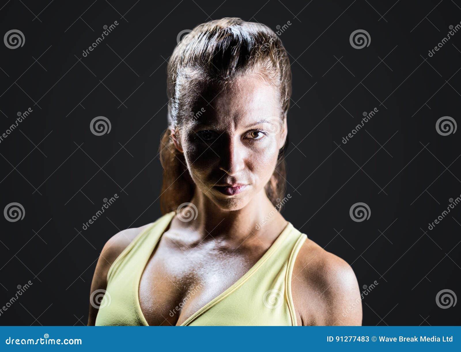 Kvinna i hårt ljus mot mörk grå bakgrund