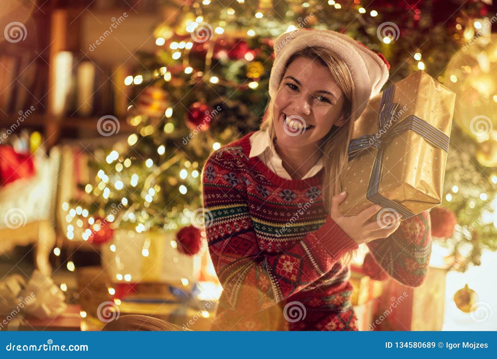 Kvinna i jultomten hatt med julklappar