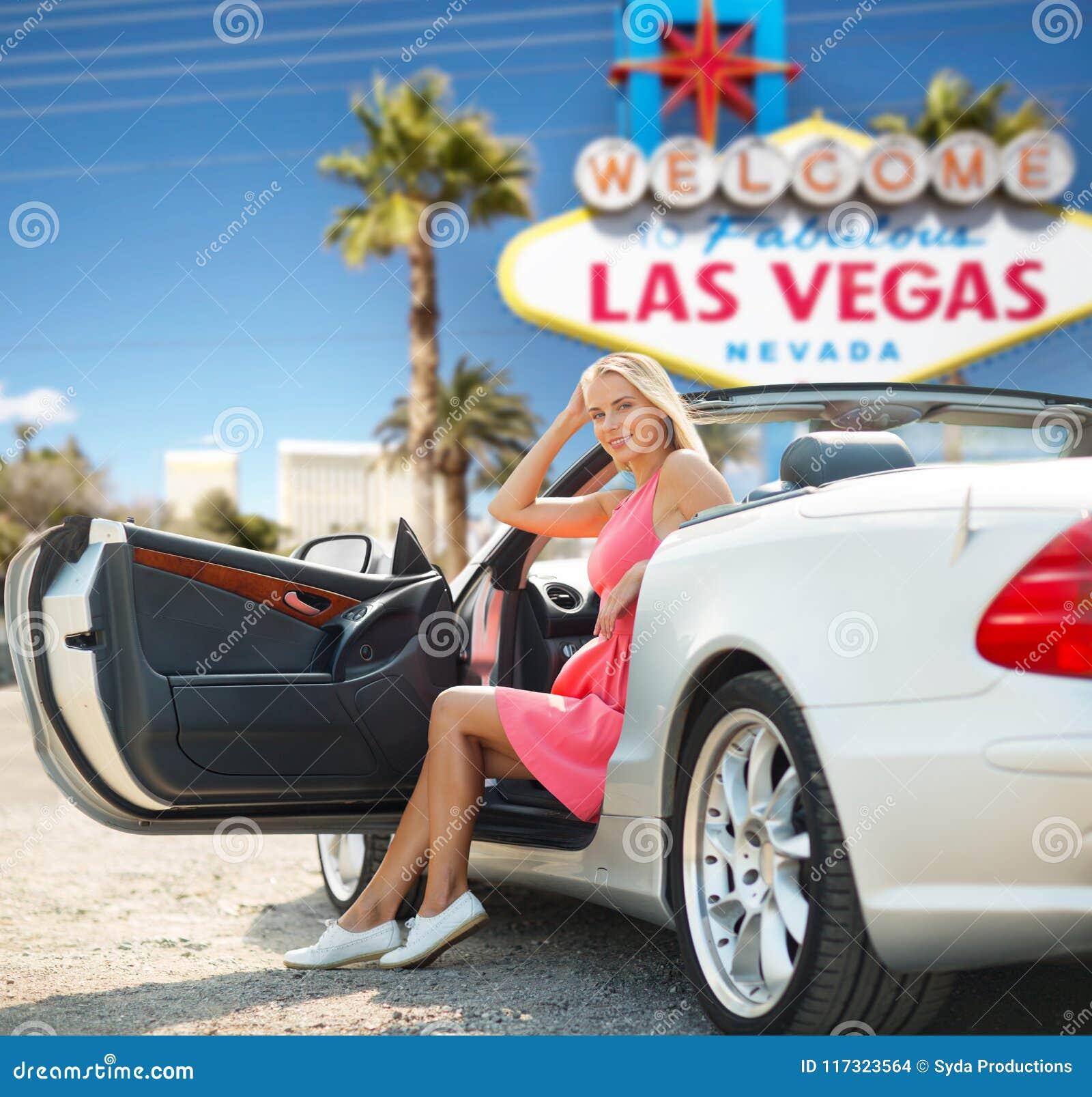 Kvinna i konvertibel bil över det Las Vegas tecknet