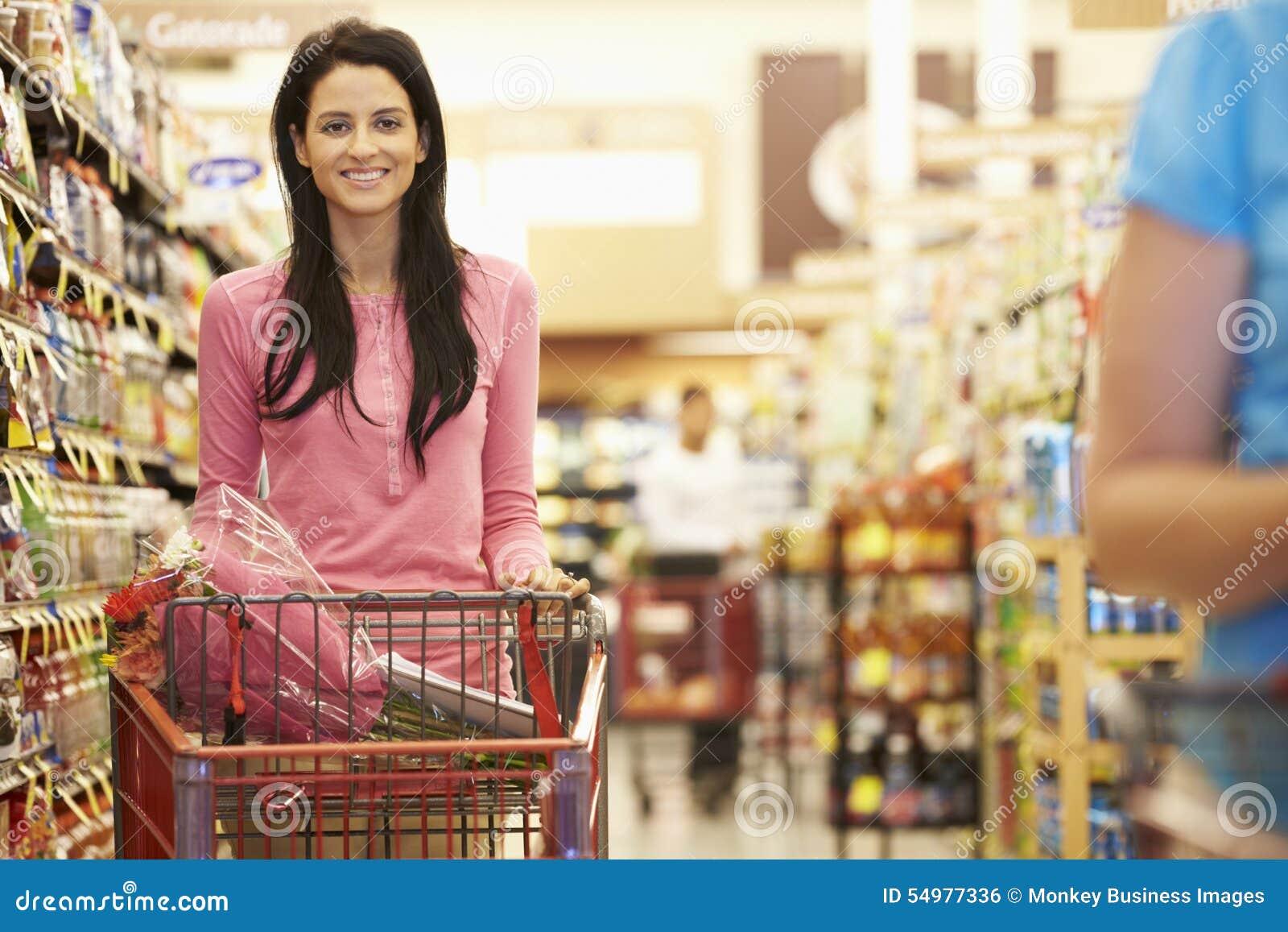 Kvinna i livsmedelsbutikgång av supermarket