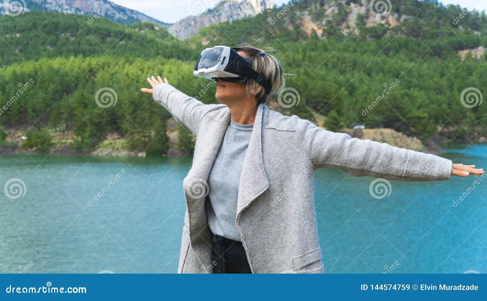 Kvinna i naturen som bär ökad verklighetskyddsglasögon