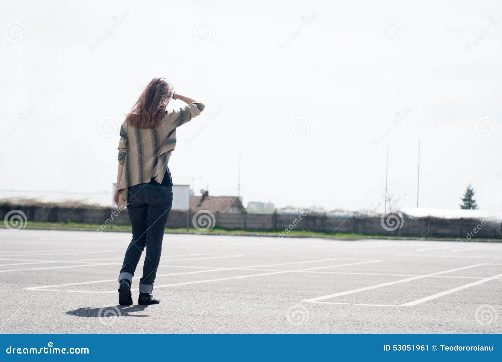 Kvinna i parkeringsplatsen