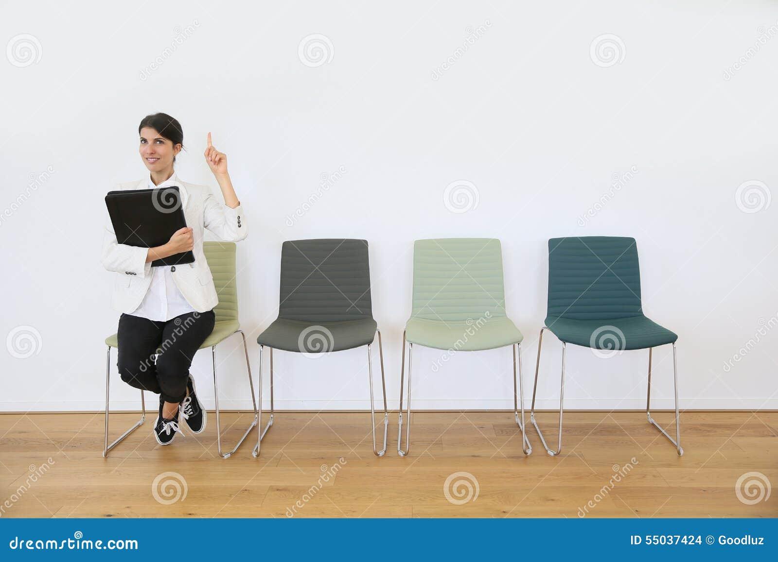 Kvinna i poiting finger för väntande rum upp, idé