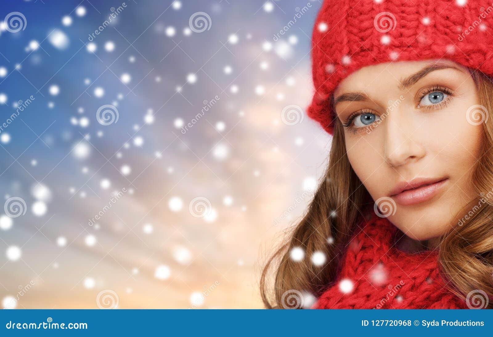 Kvinna i röd hatt och halsduk över snöbakgrund