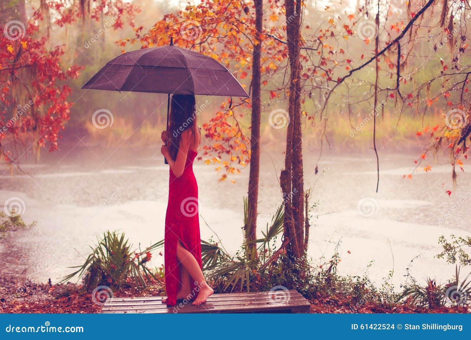 Kvinna i röd klänning med paraplyet