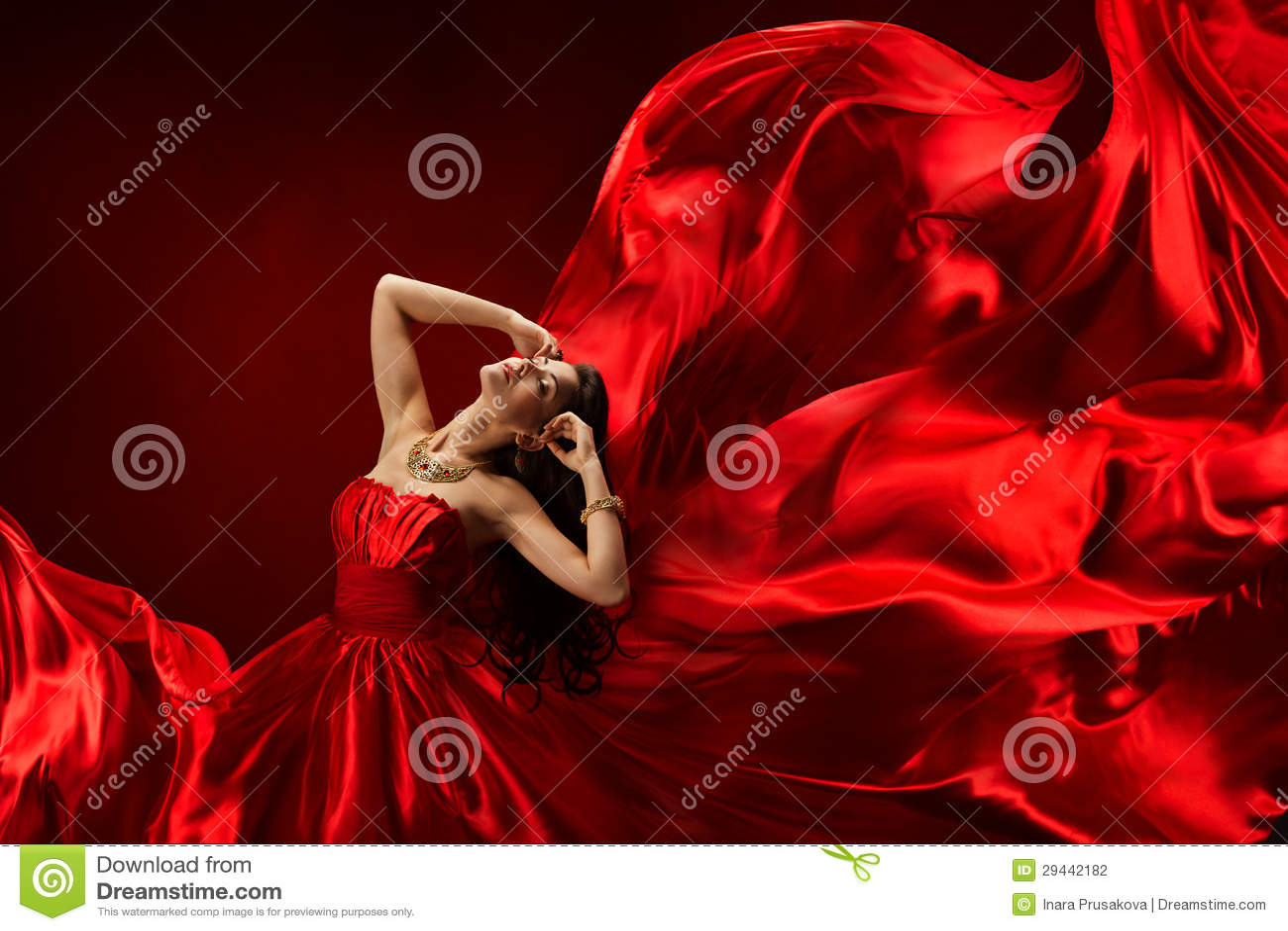 Kvinna i röd klänning som blåser med flygtyg