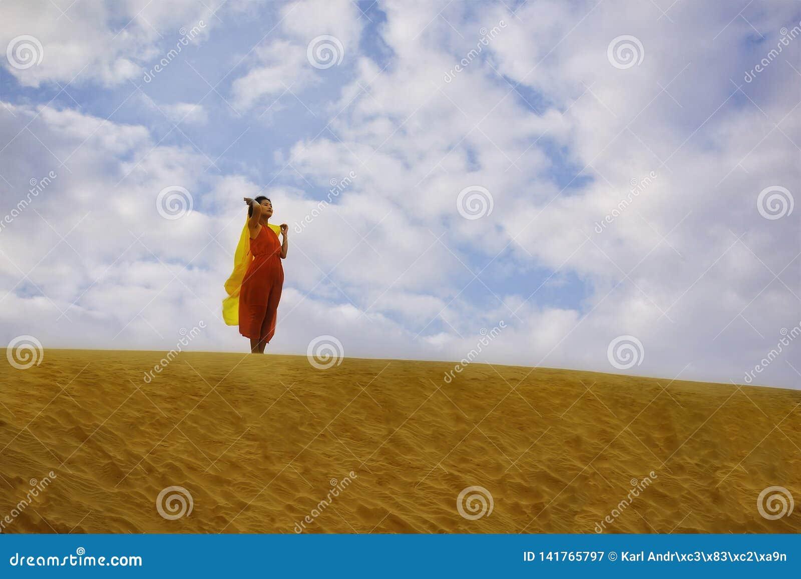 Kvinna i rött klänninganseende i öknen