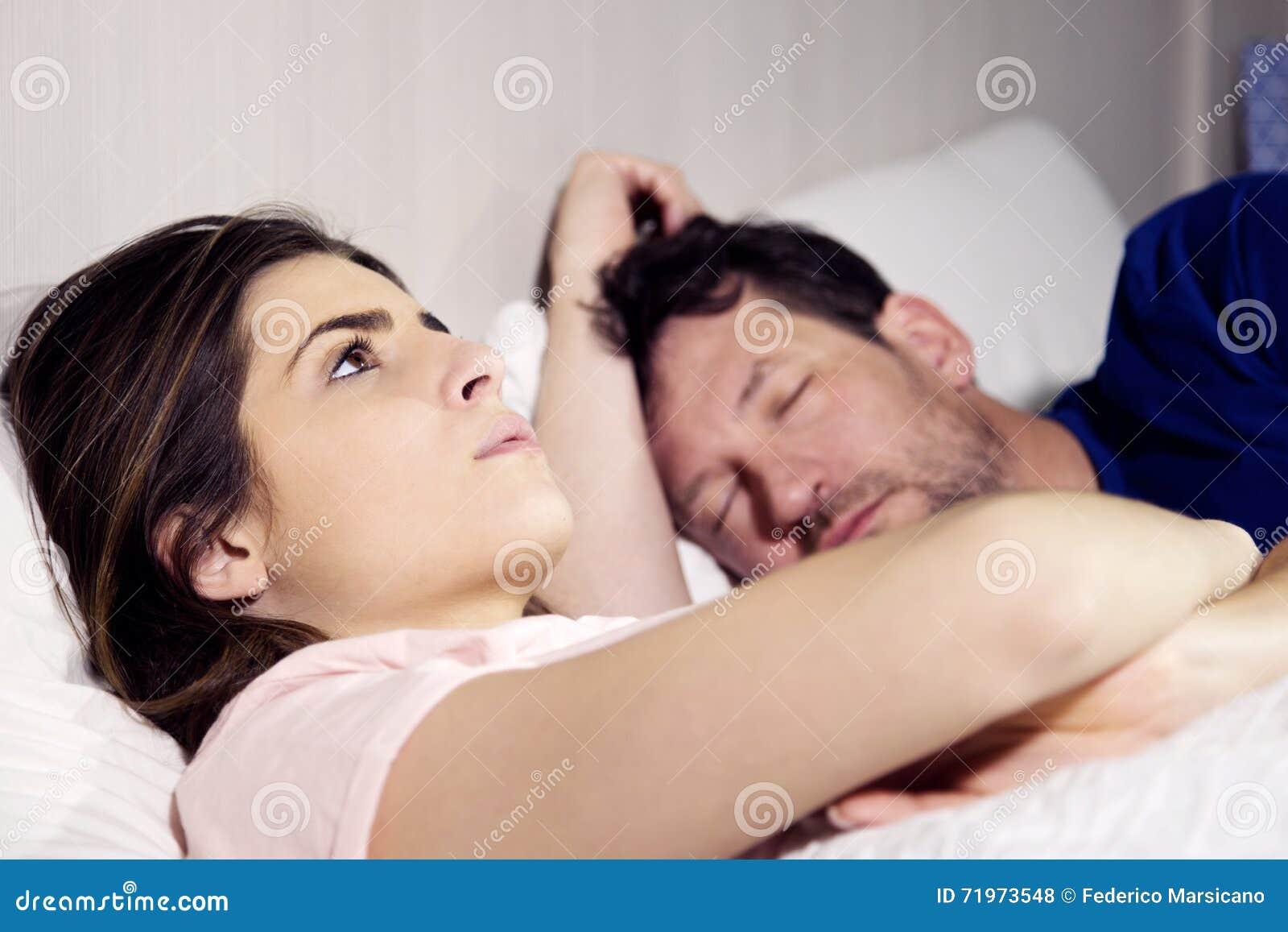 Kvinna i säng med pojkvännen som tänker om förhållande, medan mannen sover