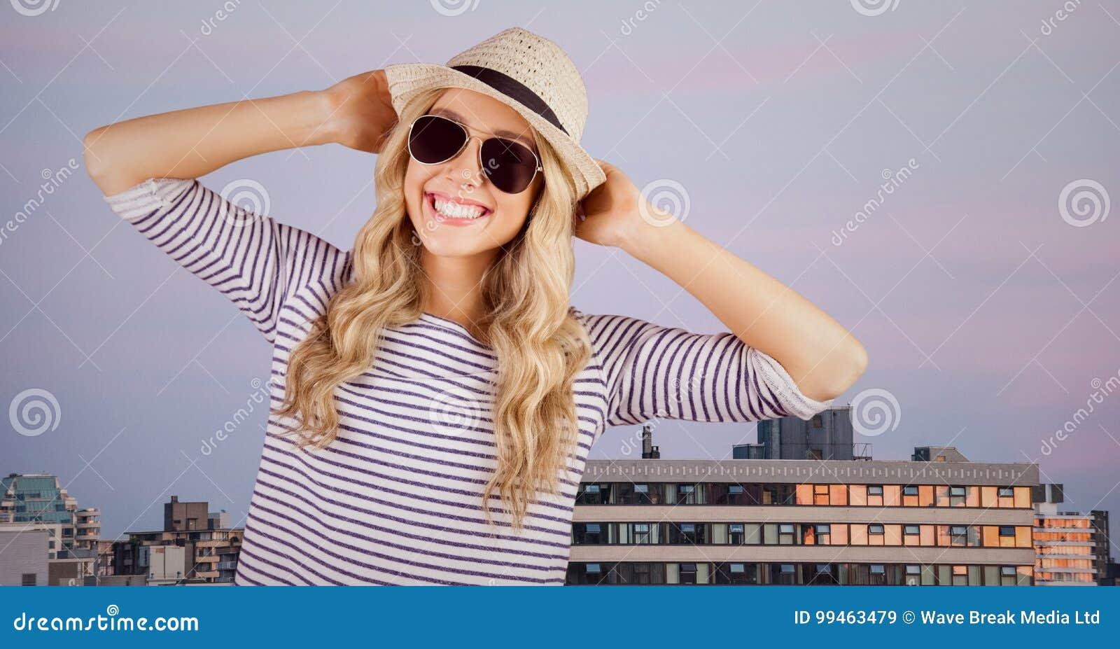 Kvinna i sommarkläder med händer på huvudet mot byggnader och aftonhimmel
