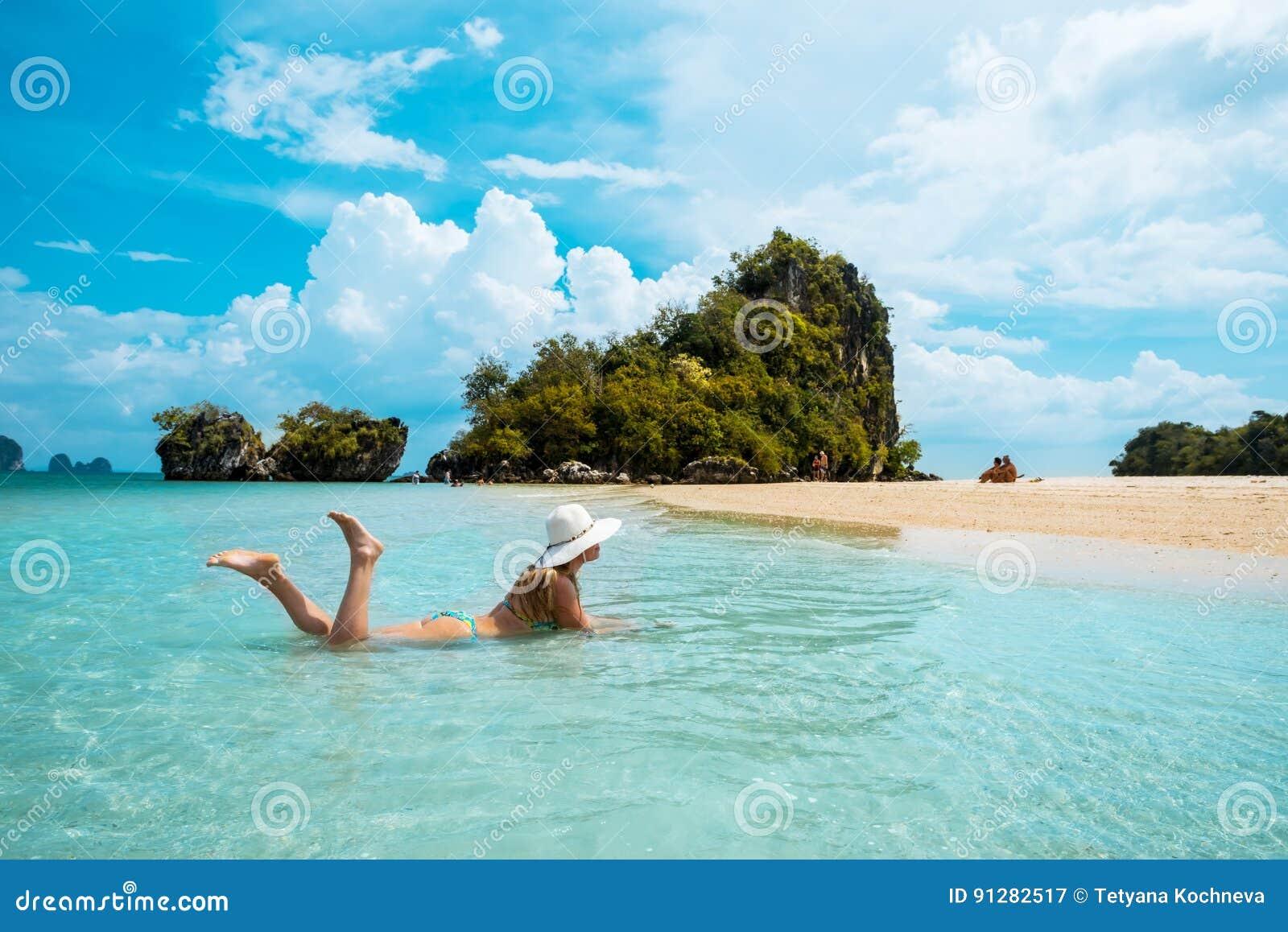Kvinna i sugrörhatt som vilar den tropiska Thailand stranden