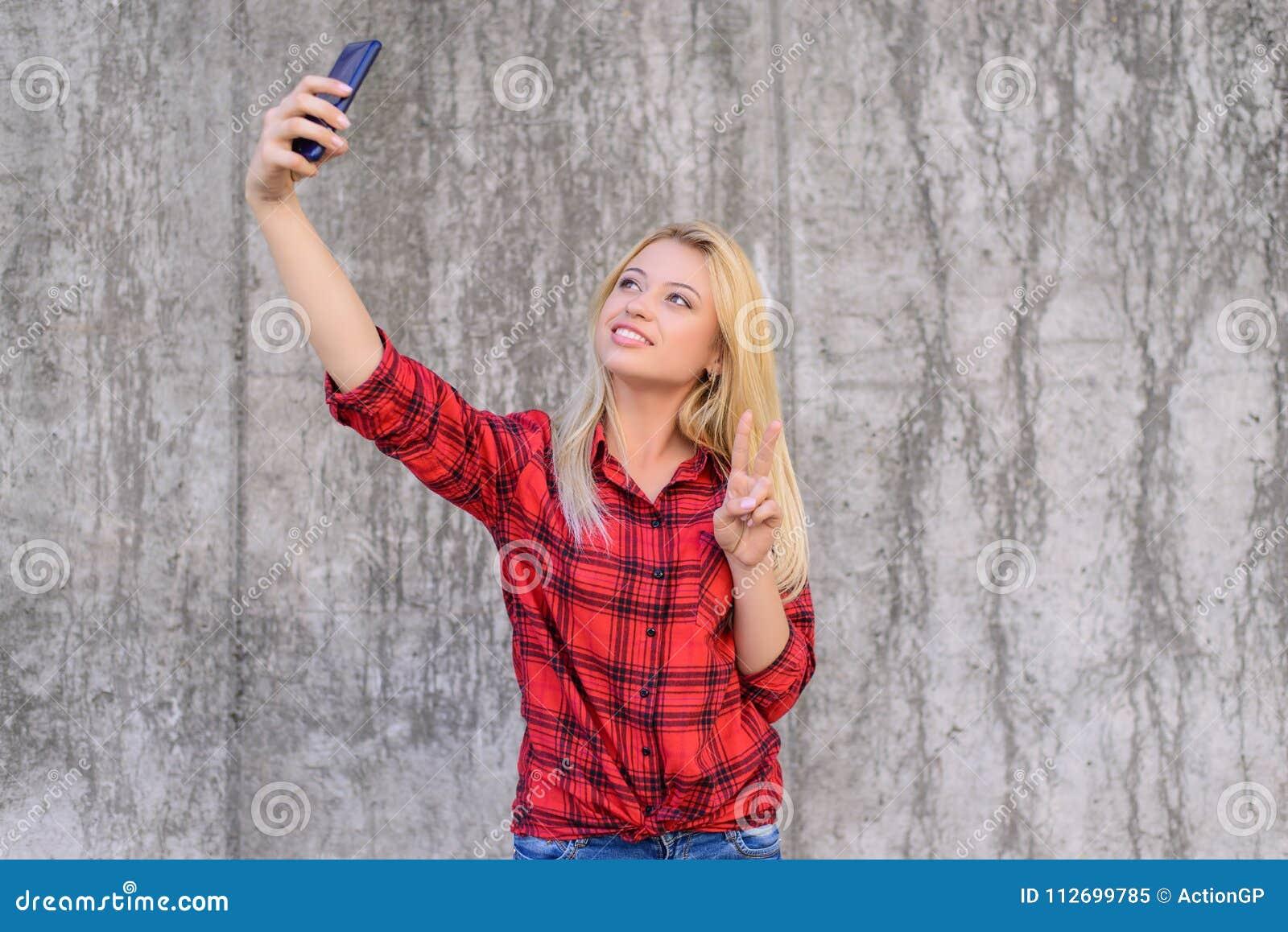 Kvinna i tillfällig kläder med att stråla taling selfie för leende på hennes smartphone och uppvisning v-tecken cellmobiltelefon