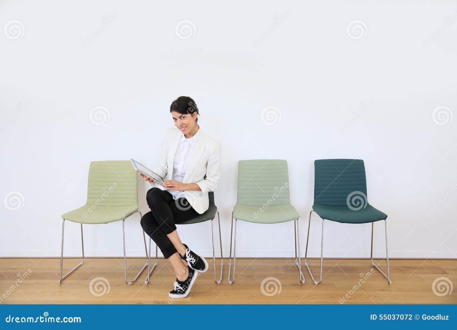 Kvinna i väntande rum med minnestavlan