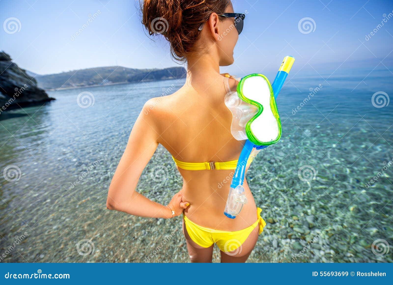 Kvinna med att snorkla maskeringen nära havet