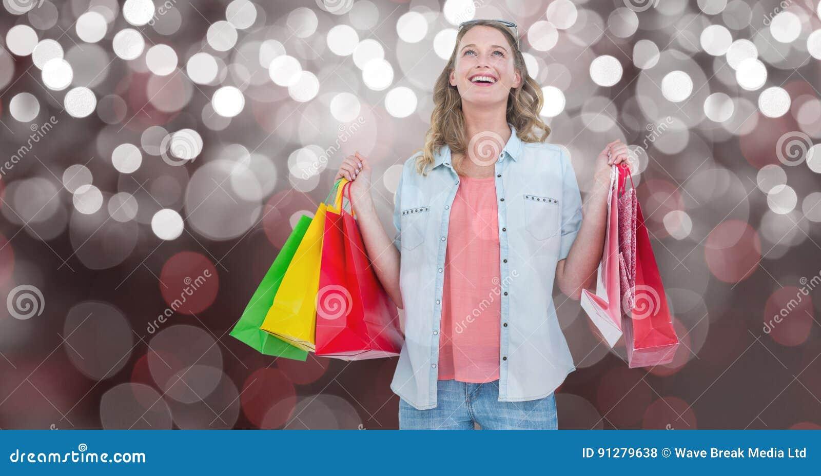 Kvinna med bärande shoppingpåsar över bokeh