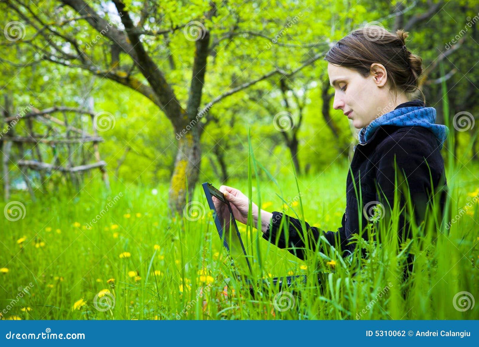 Kvinna med bärbar dator i fält