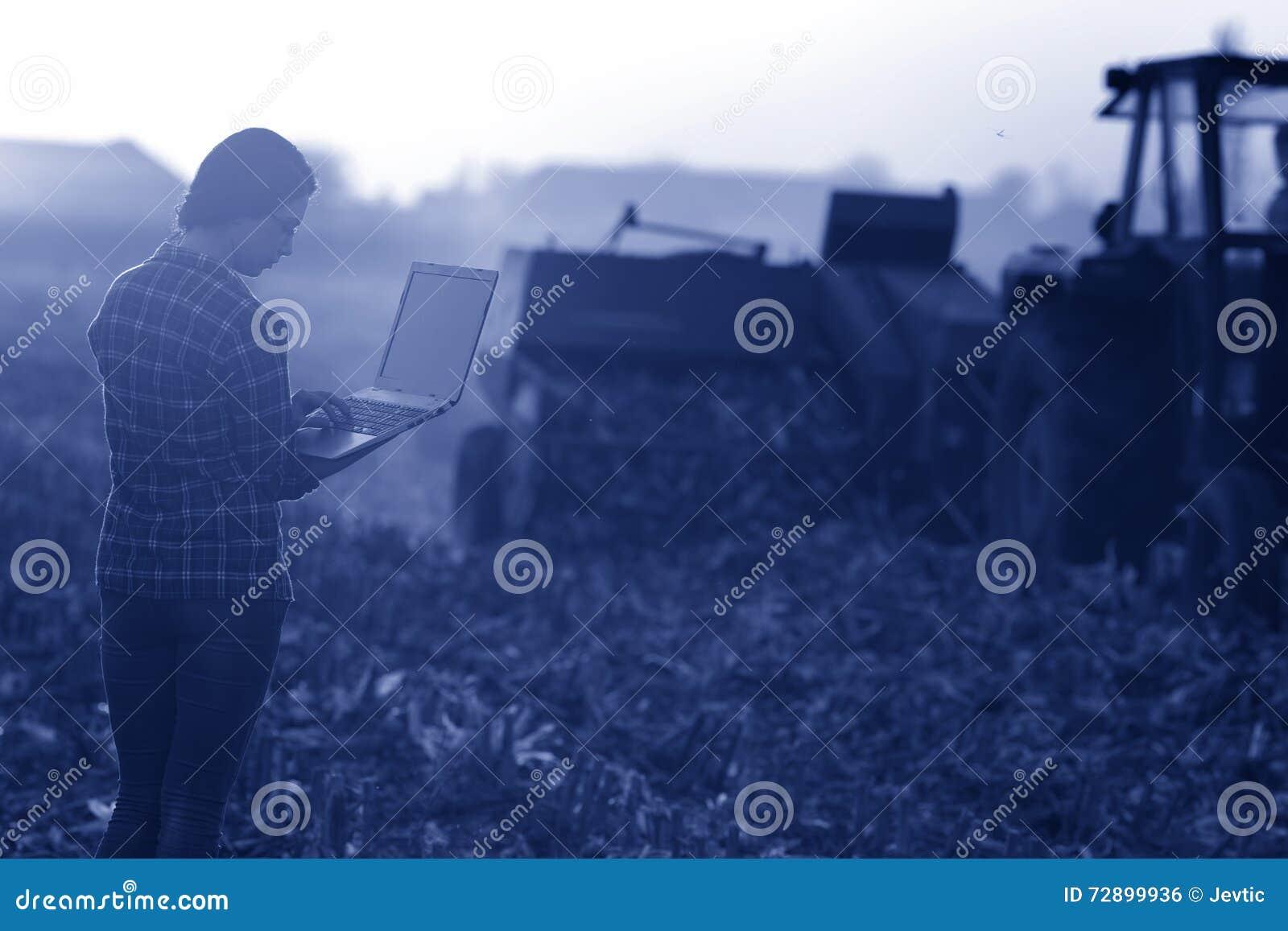 Kvinna med bärbara datorn i fältet