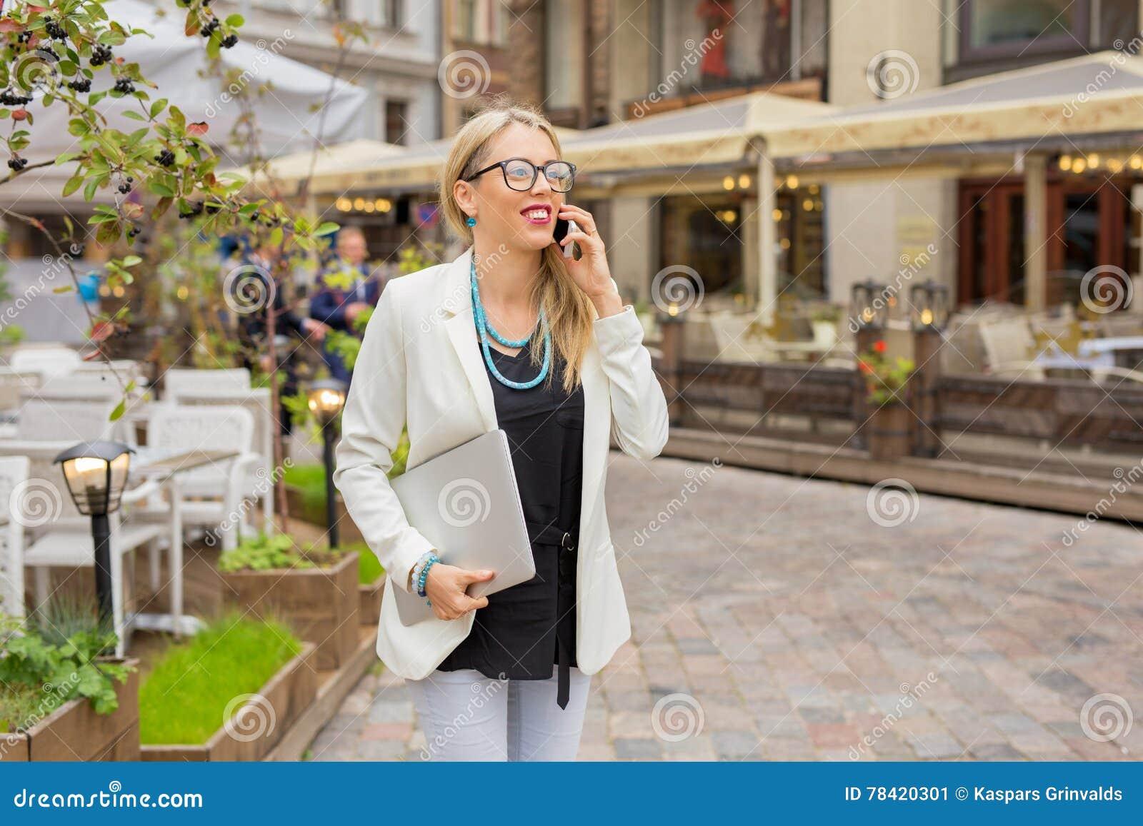 Kvinna med bärbara datorn i hennes hand som talar på telefonen
