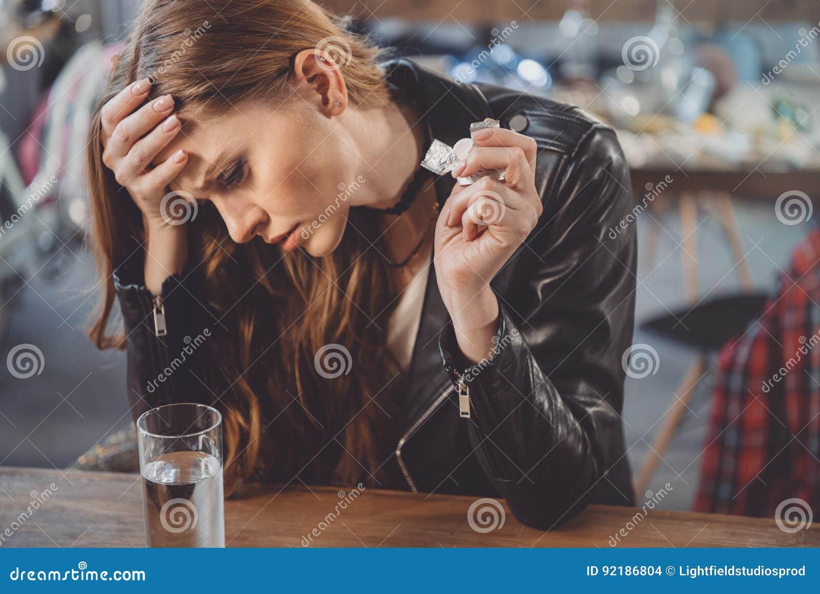Kvinna med bakrus med mediciner i smutsigt rum