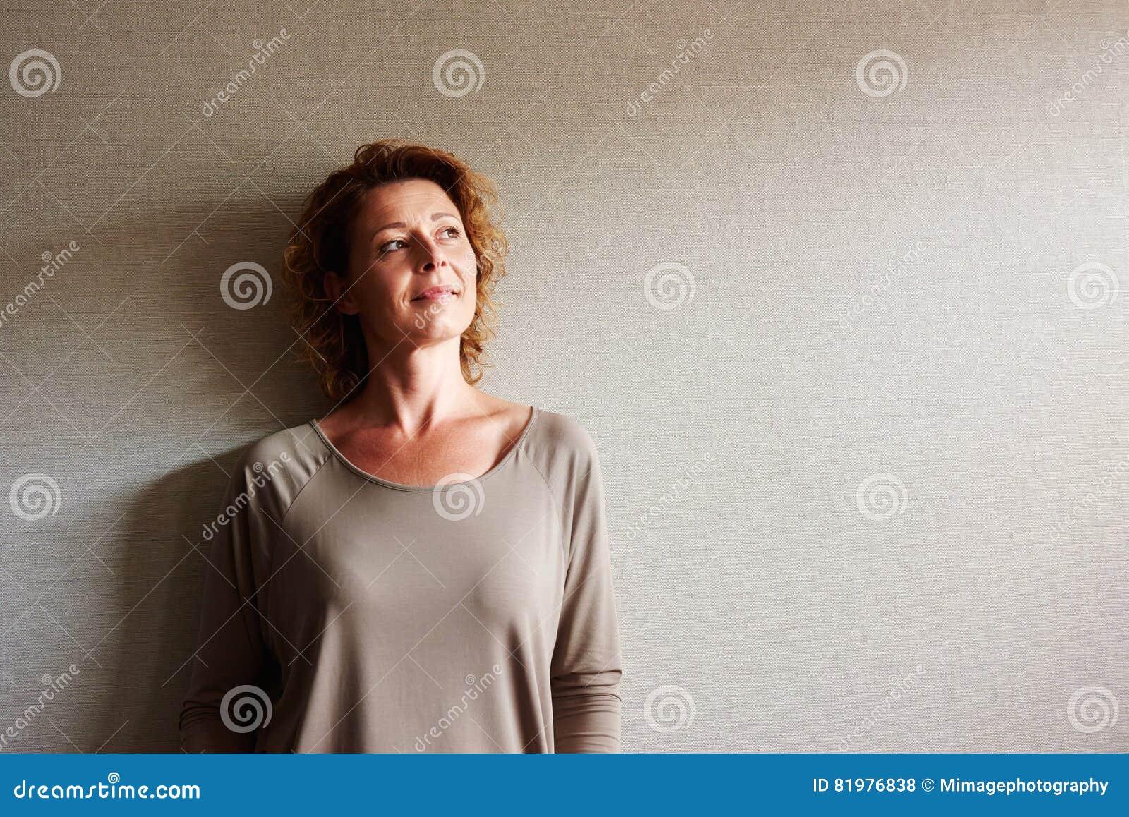 Kvinna med benägenhet för lockigt hår på väggen i begrundande