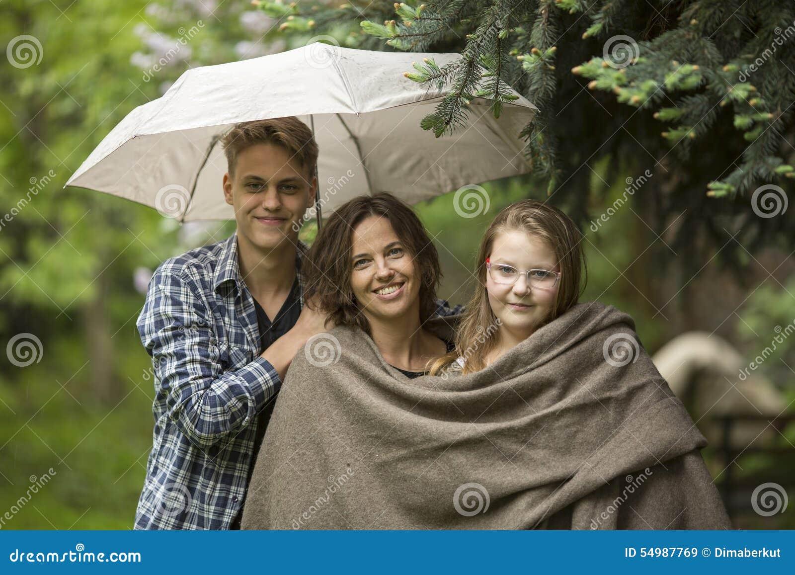 Kvinna med deras vuxna barn, dotter och son, i parkera under ett paraply Lyckligt