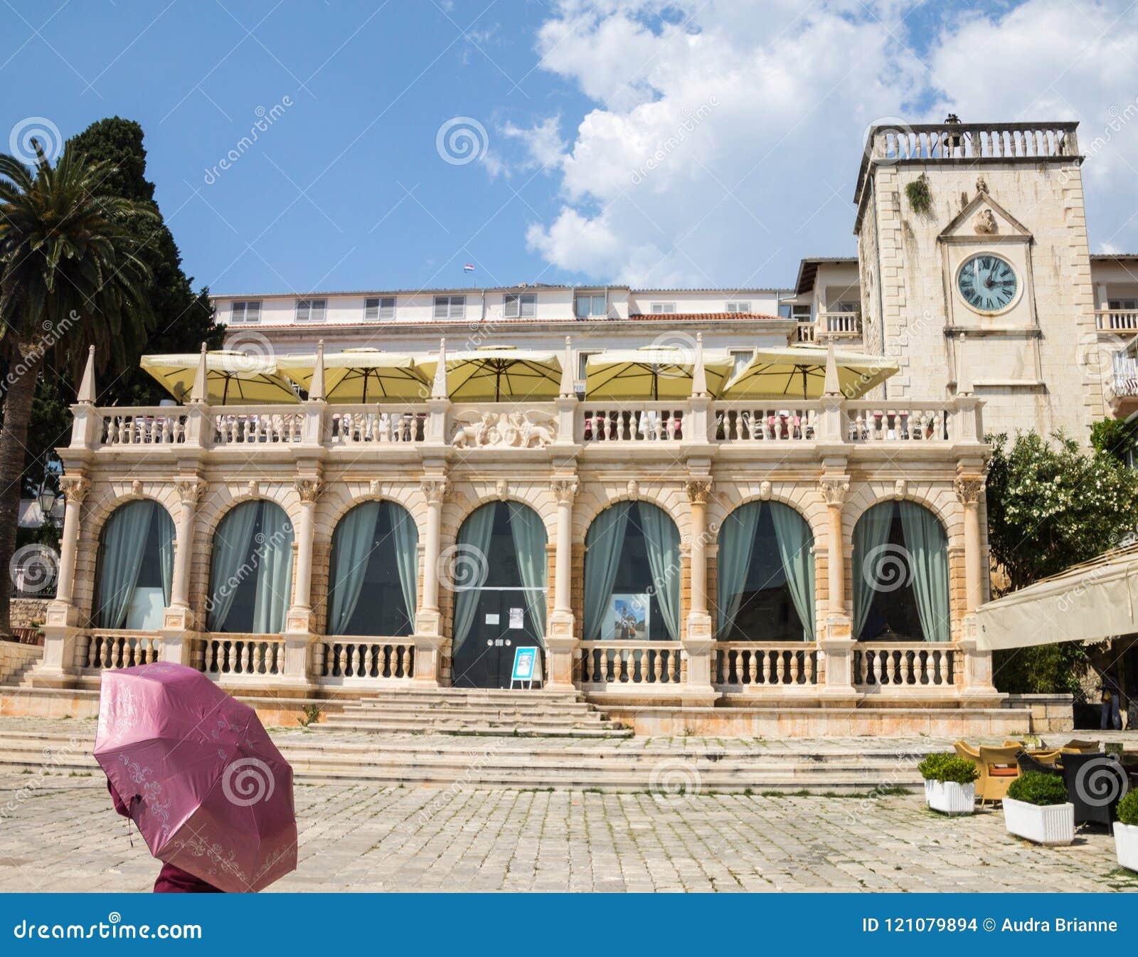Kvinna med det rosa paraplyet som är främst av stenloggia i Hvar, Kroatien
