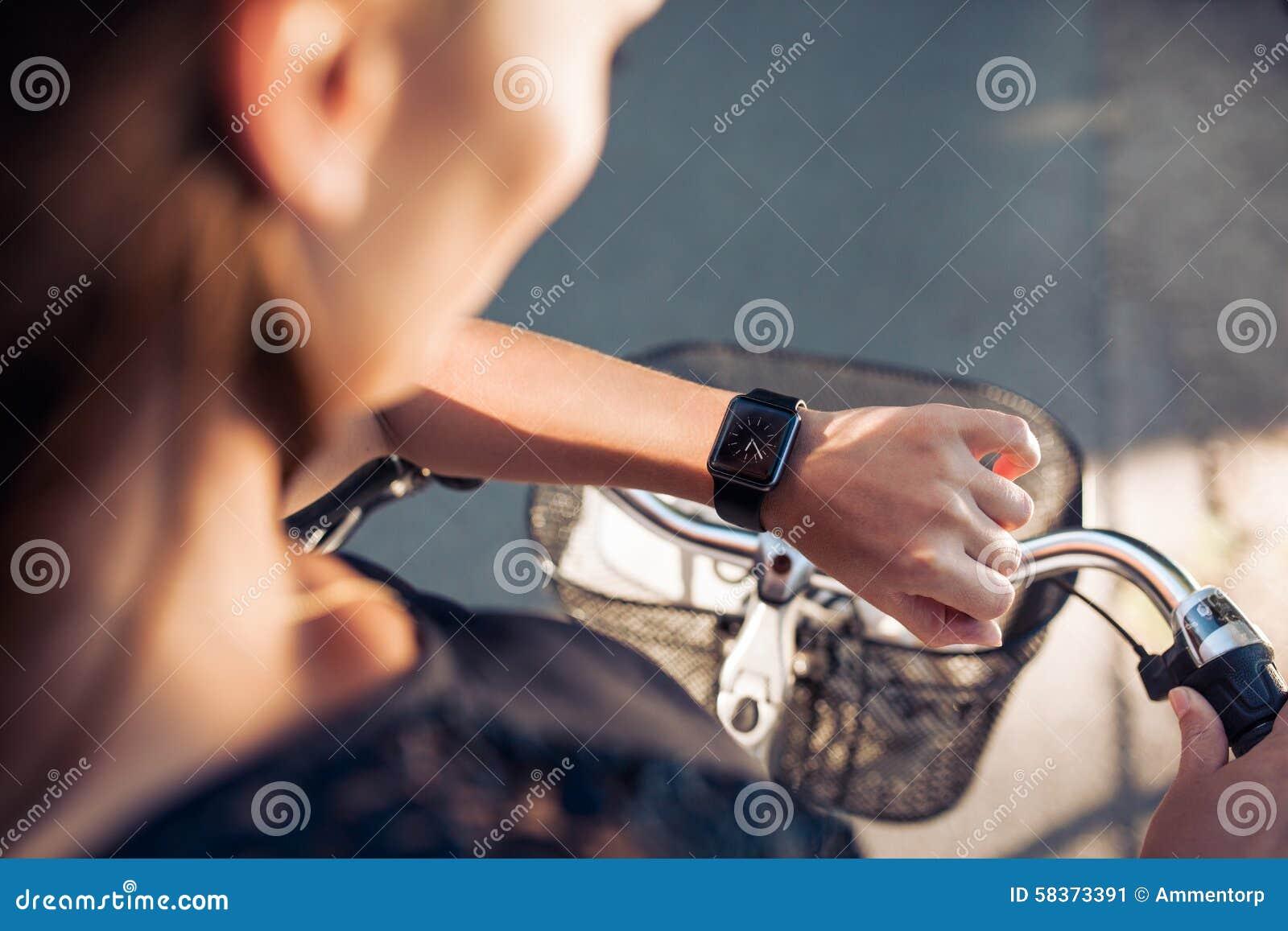 Kvinna med en cykel som ser hennes smartwatch