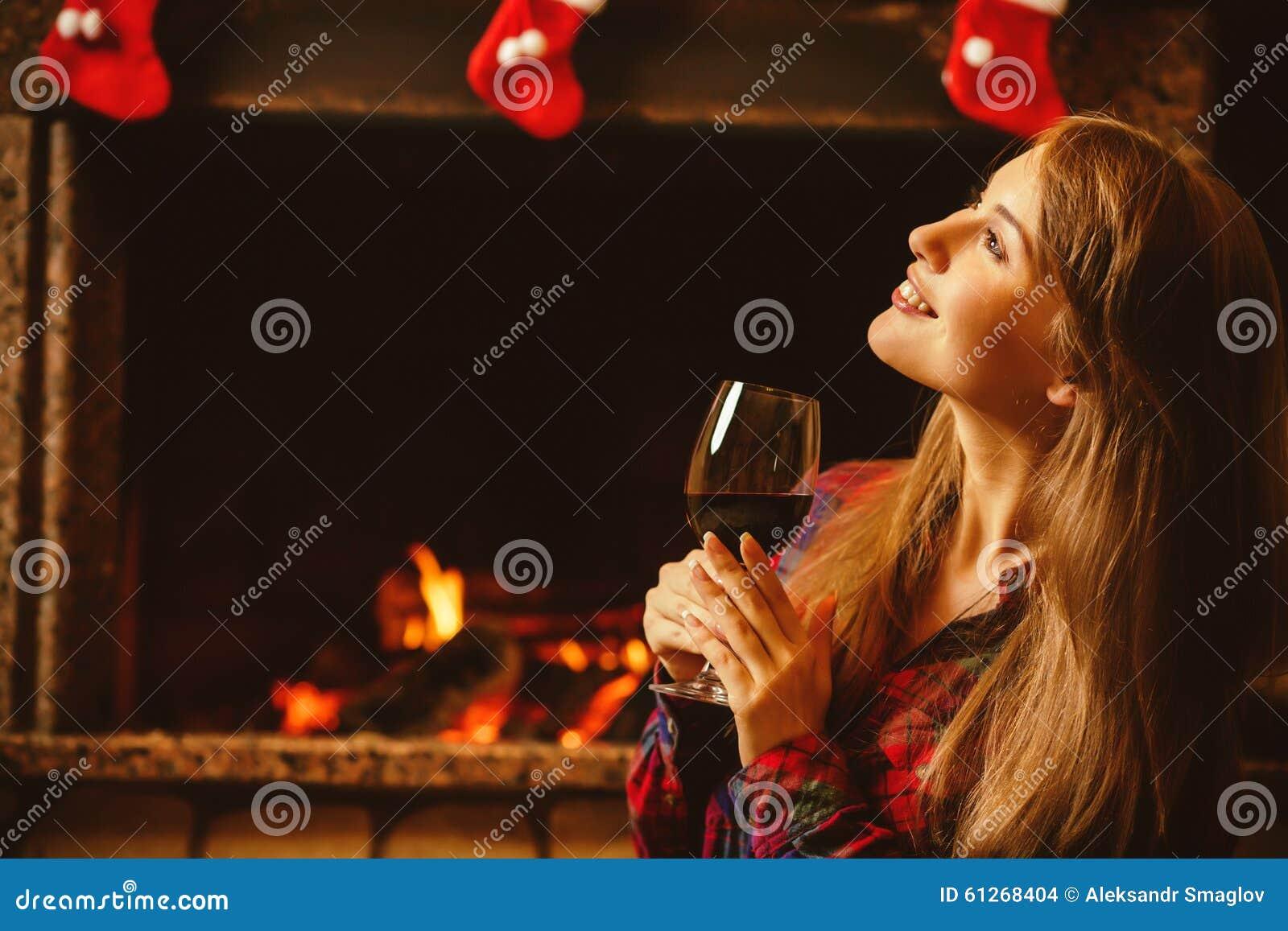 Kvinna med ett exponeringsglas av vin vid spisen Ung attraktiv wo