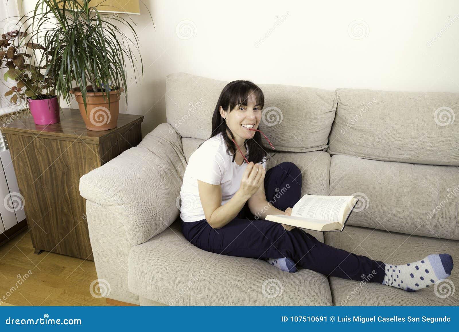 Kvinna med exponeringsglas som läser en bok på en soffa
