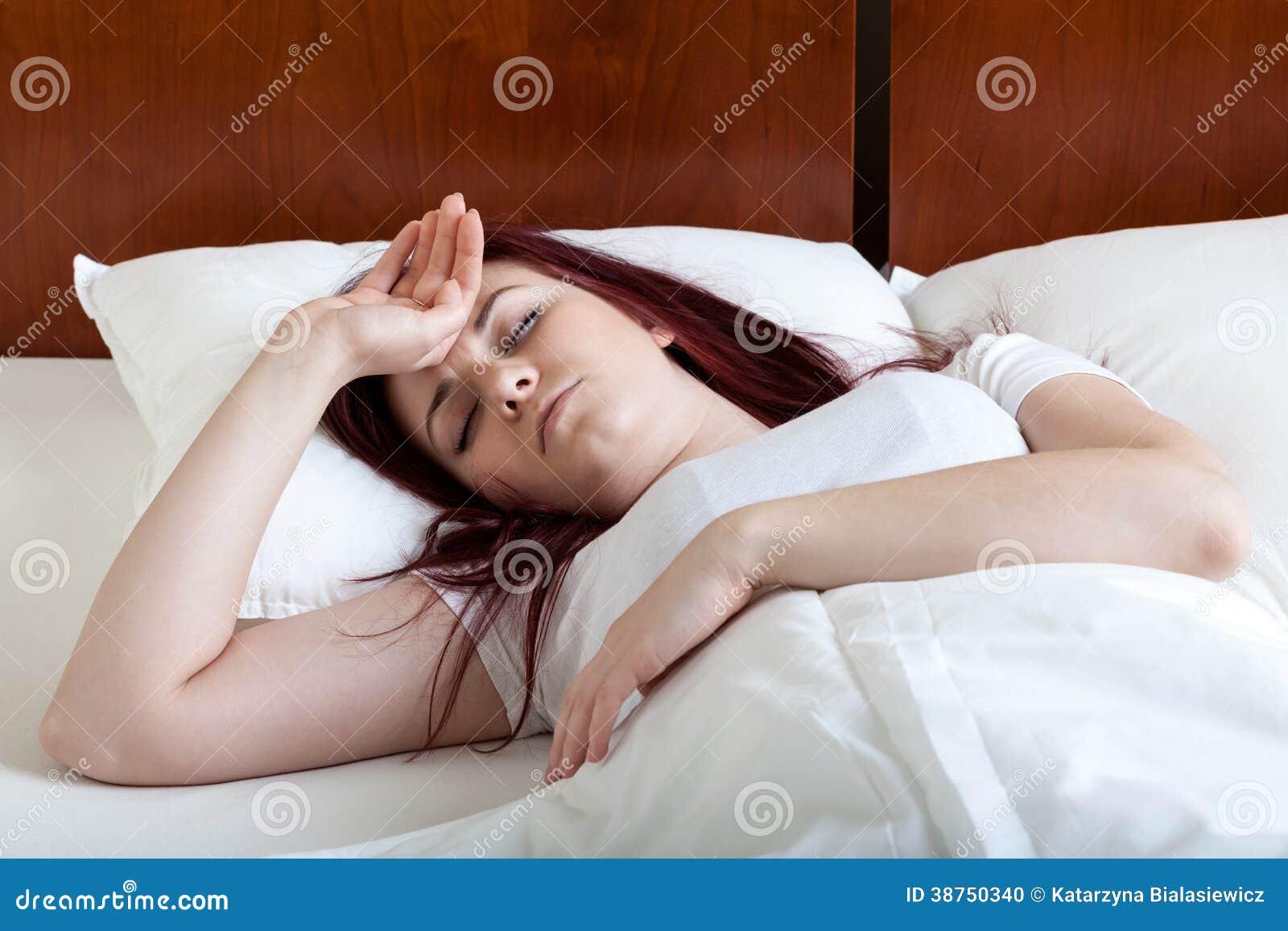 Kvinna med feber som ligger i säng