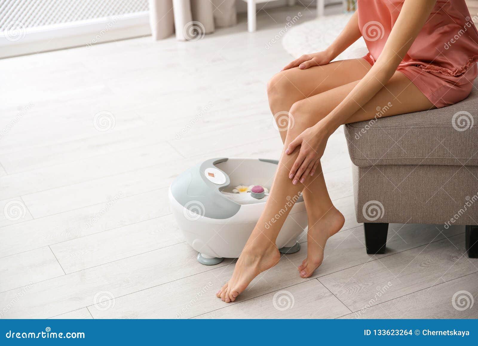 Kvinna med härliga ben som hemma sitter nära fotbad, closeup med utrymme för text