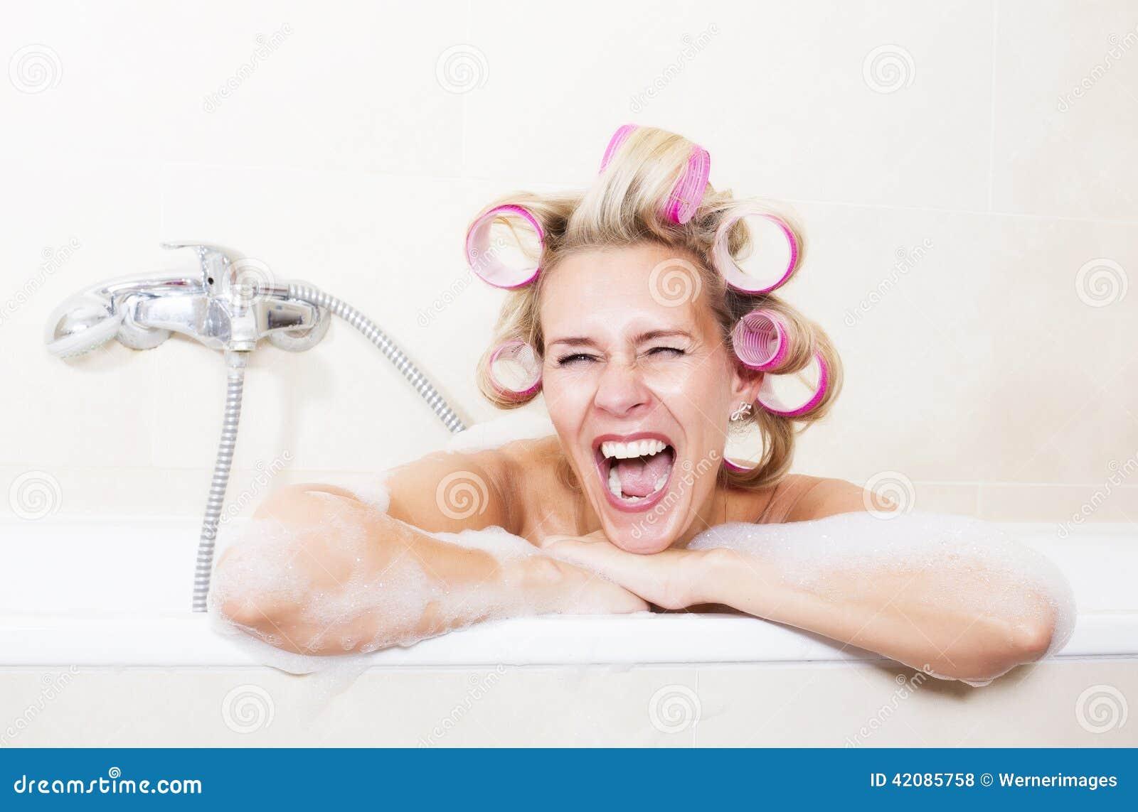 Kvinna med hårrullar i badkar