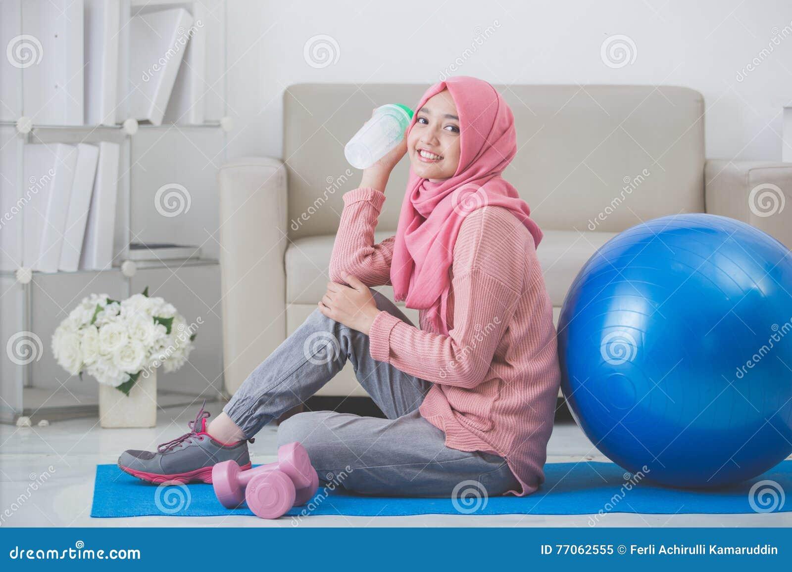 Kvinna med hijab som hemma gör övning