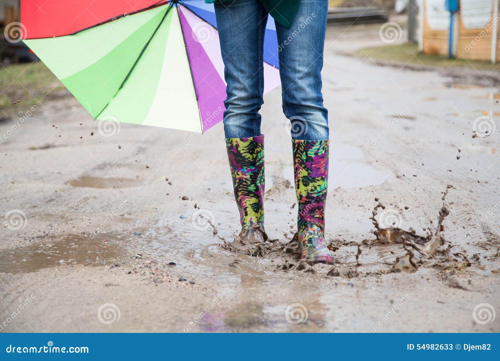 Kvinna med hopp för regnkängor