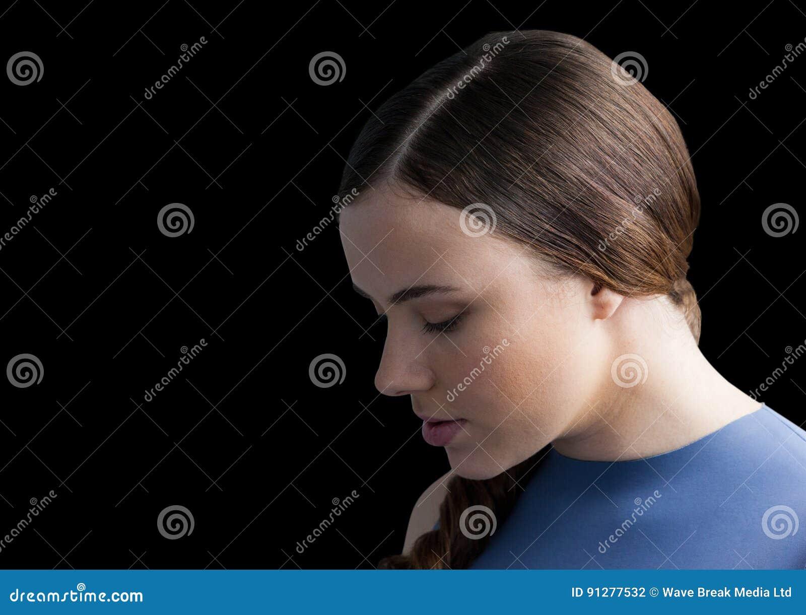 Kvinna med huvudet ner mot svart bakgrund