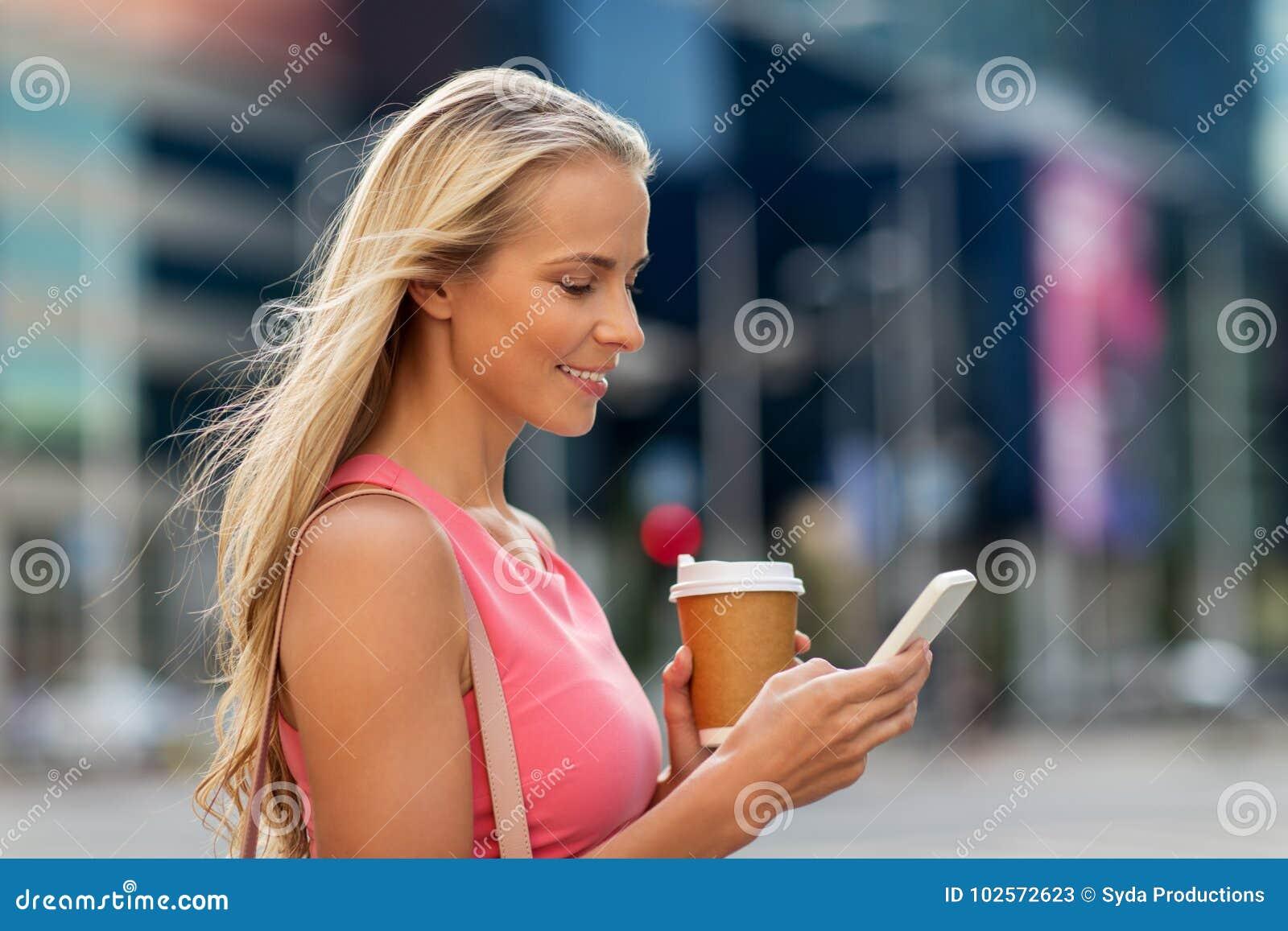 Kvinna med kaffe och smartphonen i stad
