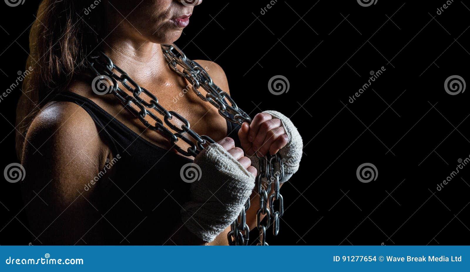 Kvinna med kedjor mot svart bakgrund