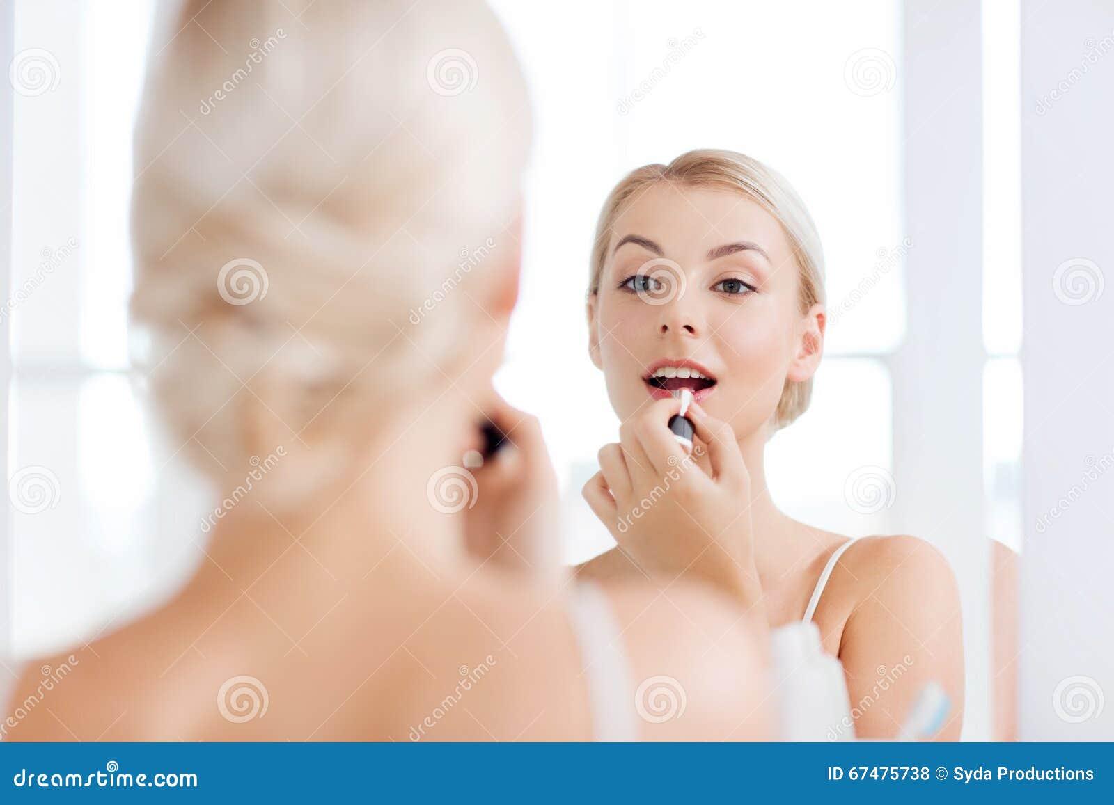 Kvinna med läppstift som applicerar smink på badrummet