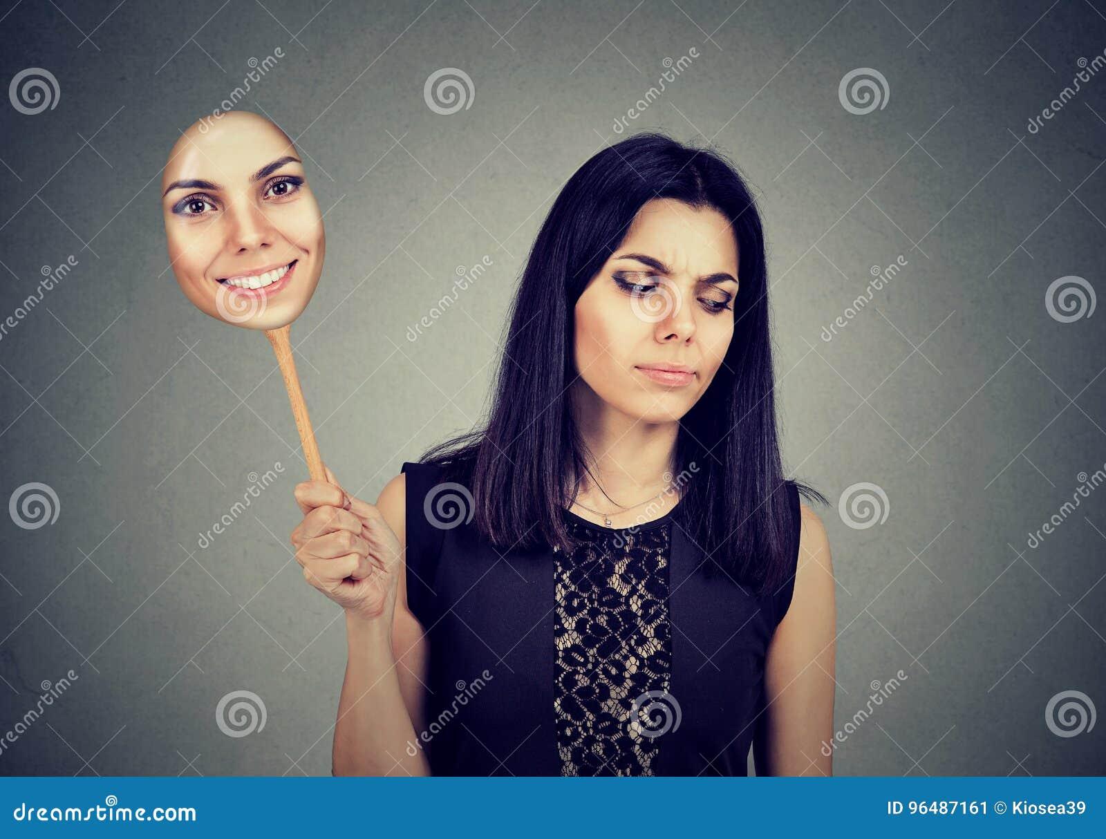 Kvinna med ledset ta för uttryck av en maskering som uttrycker gladlynthet