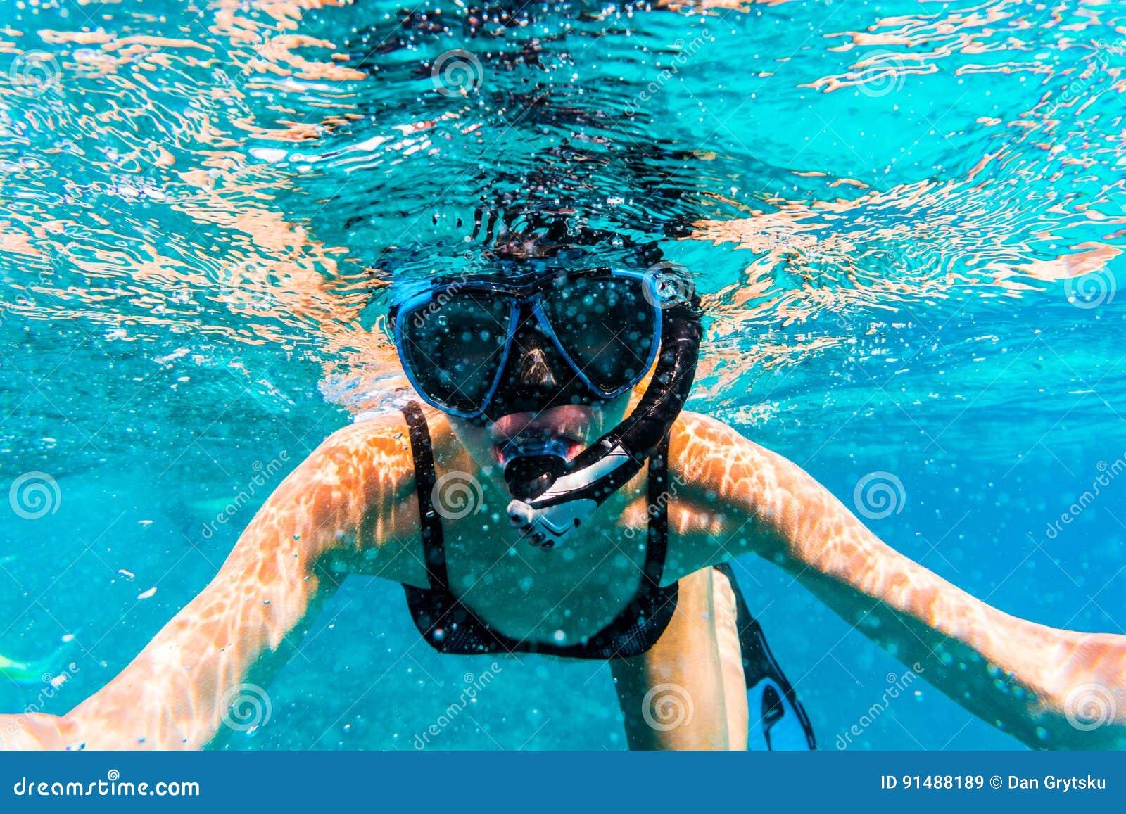 Kvinna med maskeringen som snorklar i klart havsvatten
