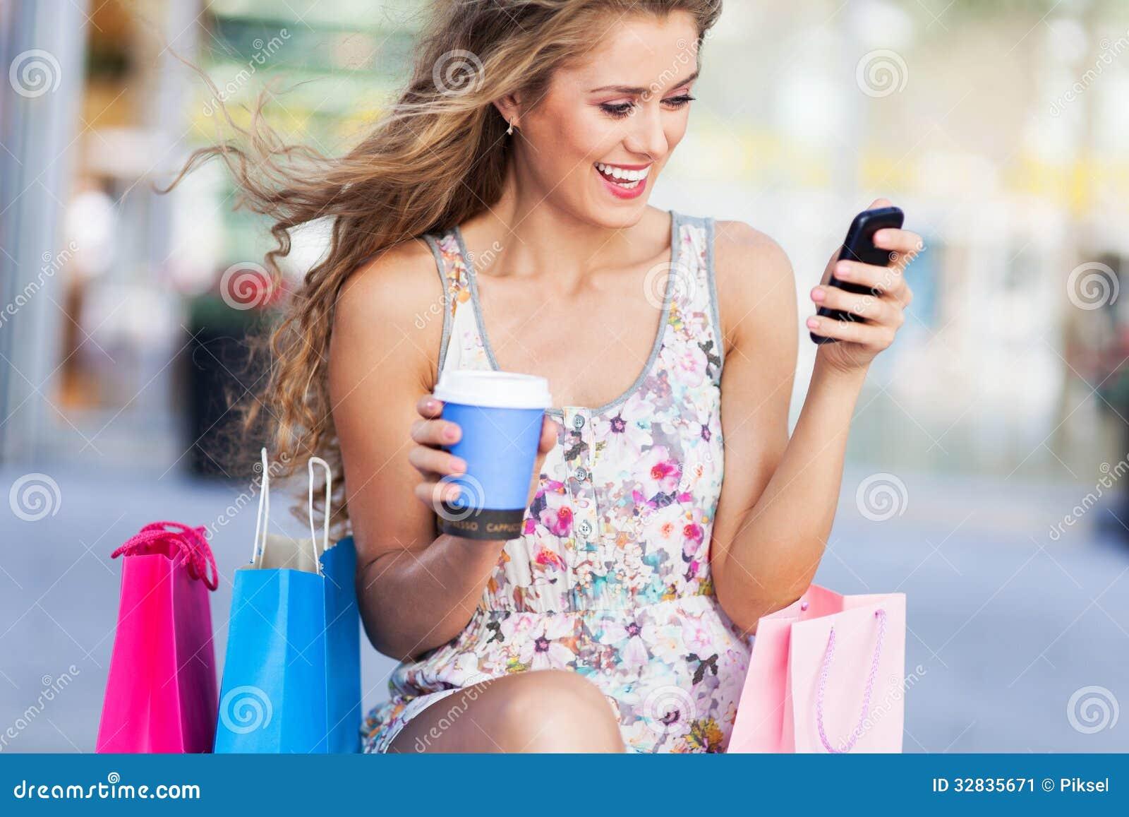 Kvinna med mobiltelefon- och shoppingpåsar