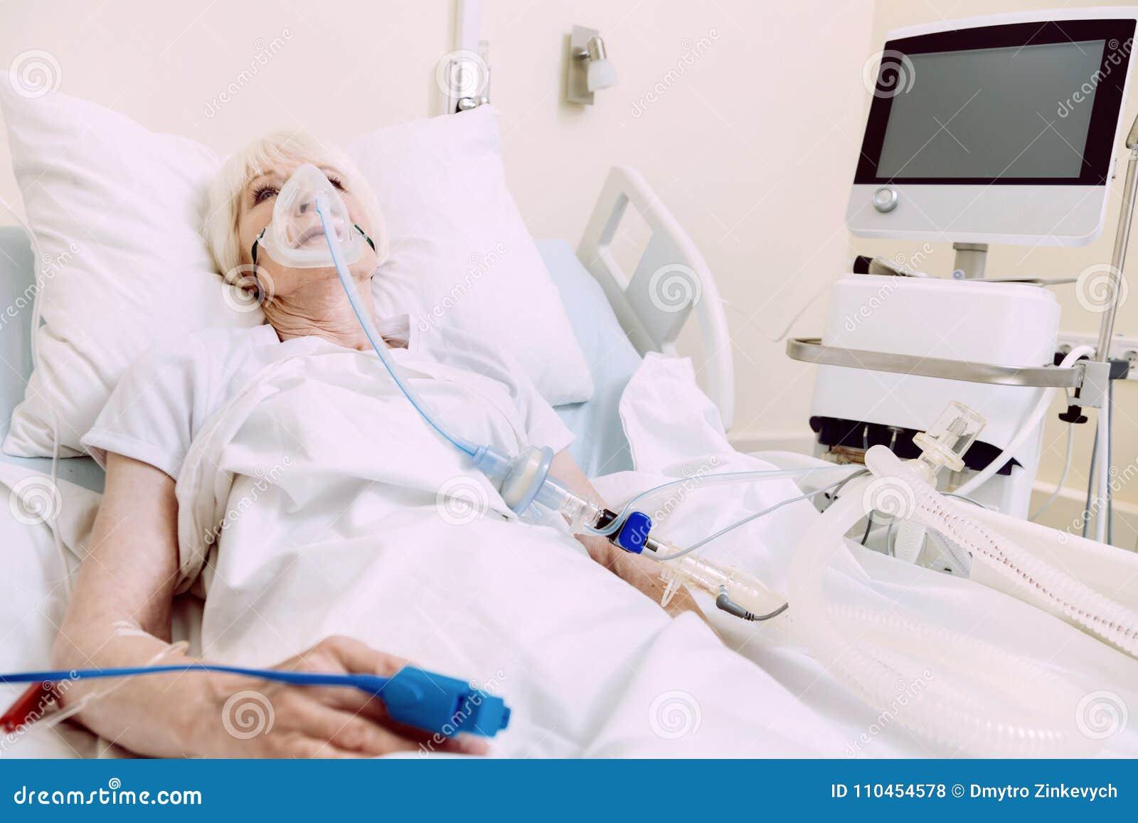 Kvinna med respiratorisk service som genomgår behandling på sjukhuset