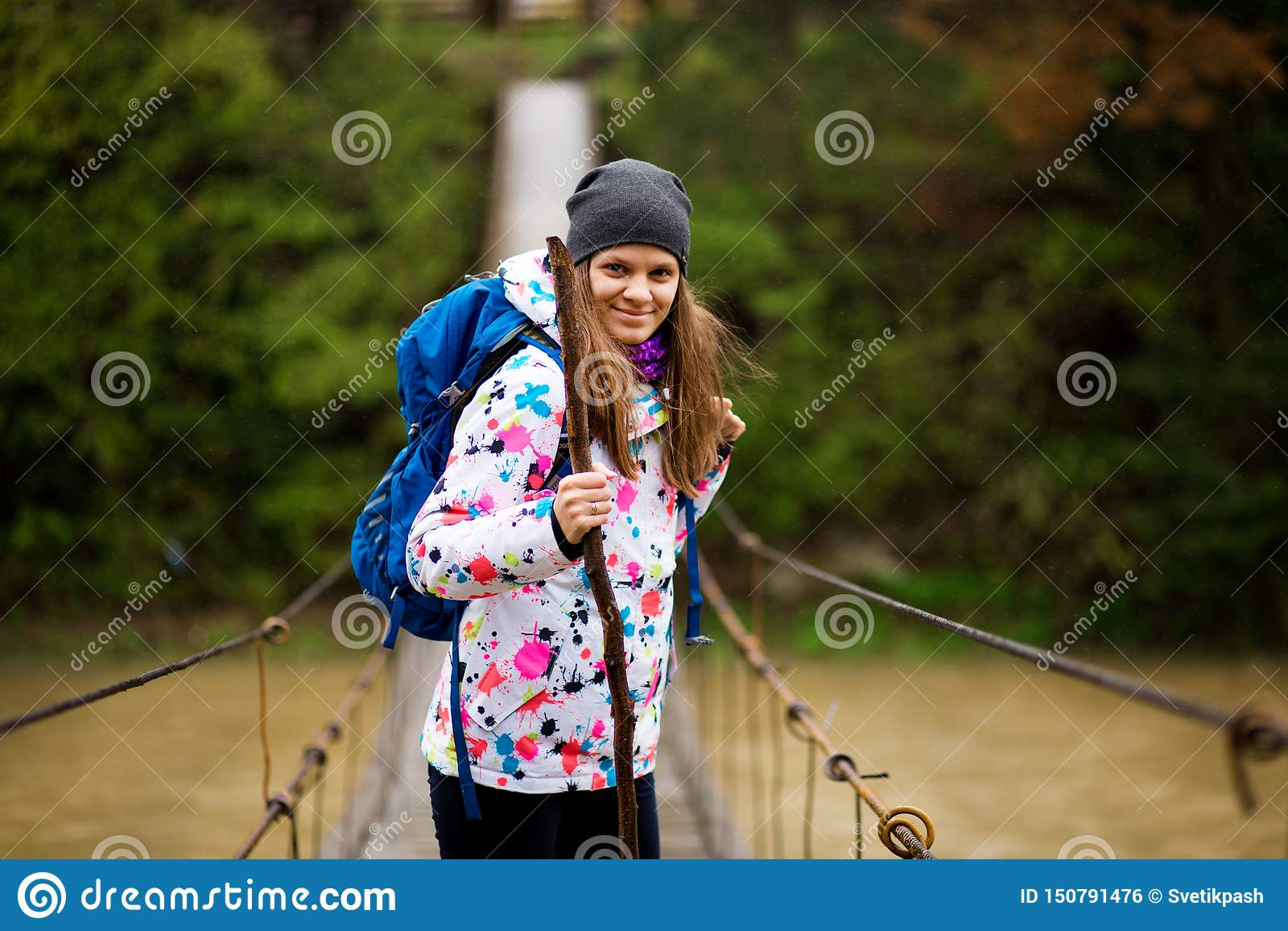Kvinna med ryggsäcken som fotvandrar skogen för livsstilaffärsföretagbegrepp och den arga floden i aktiva semestrar för skog