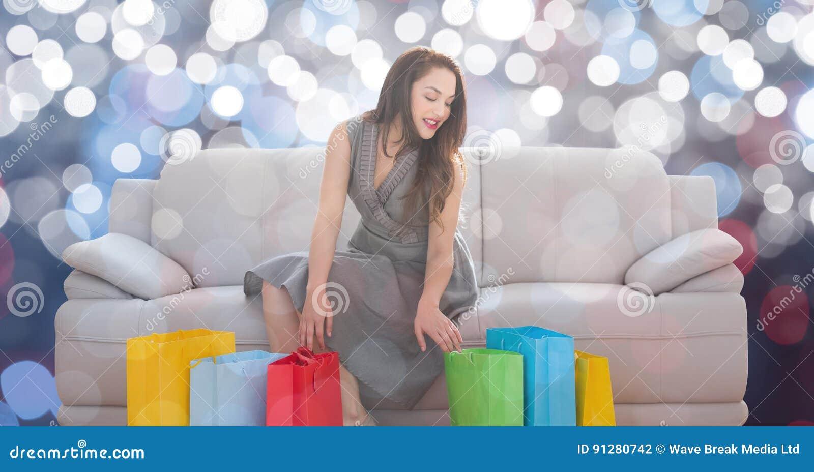 Kvinna med shoppingpåsar som sitter på soffan