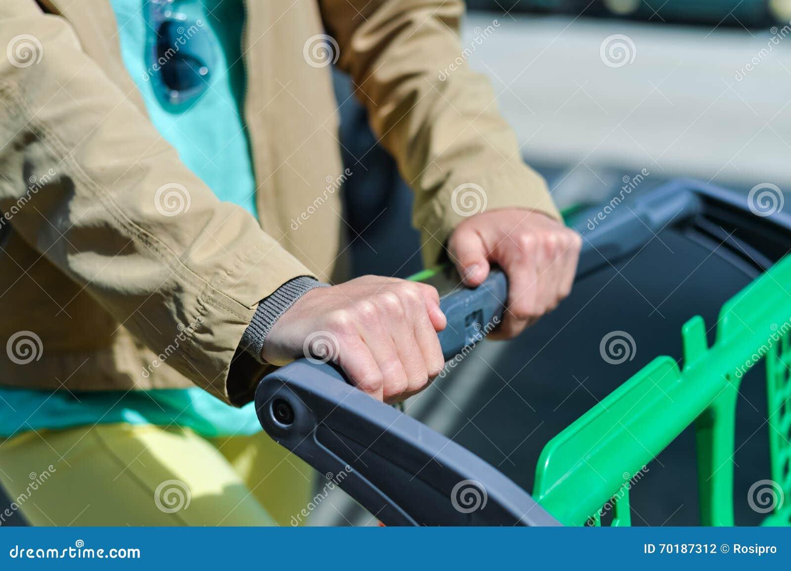 Kvinna med shoppingvagnen på bilparkering
