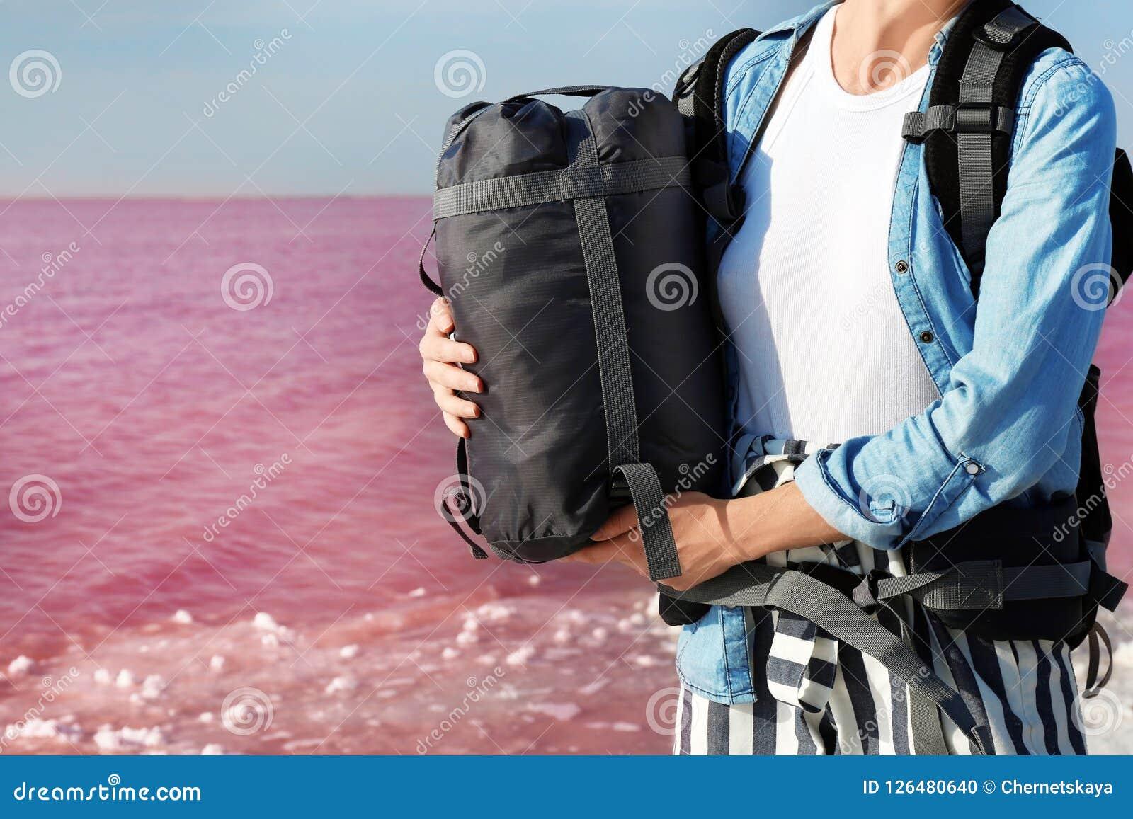 Kvinna med sovsäcken på kust