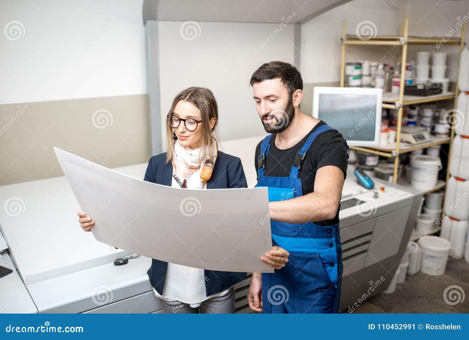 Kvinna med tryckoperatören på tillverkningen