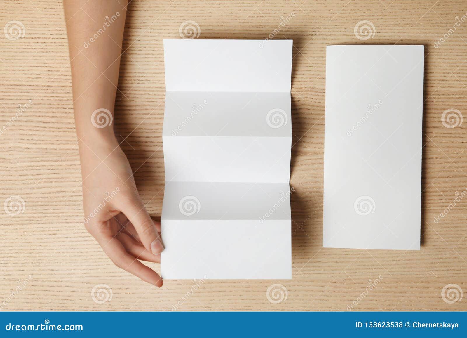 Kvinna med två tomma broschyrer på träbakgrund, bästa sikt